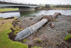 The November 2009 floods eroded the banks of the River Derwent, downstream of Cockermouth, revealing and damaging this pipeline, Cumbria, England, United Kingdom, Europe